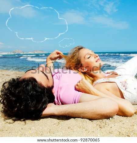 Young beautiful romantic couple relaxing on beach at sunny day. Blank cloud balloon overhead - stock photo