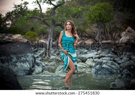 Young beautiful romantic woman in  long turquoise dress standing In a sea by the stones - stock photo