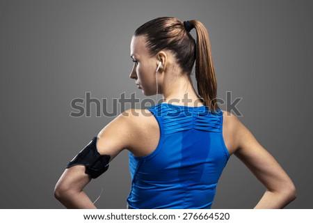Young beautiful runner. Studio shot on gray background. - stock photo