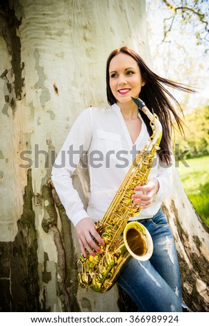 Young beautiful saxophonist with saxophone - outdoor in nature