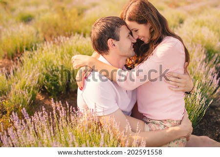 Young beautiful sensual couple outdoor kiss in windy weather in summer corn field. Young couple in love outdoor.Stunning sensual outdoor portrait of young stylish fashion couple posing in summer field - stock photo