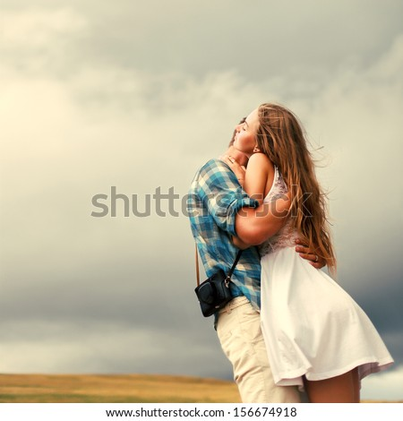 Young beautiful sensual couple standing and hugging outdoor in summer in the field together behind rainy sky - stock photo