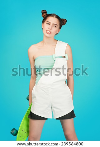 Young beautiful sensual crazy girl posing on a blue background in the studio with Longboard wearing a fashionable outfit, smiling, eyes looking to the side, the concept of youth - stock photo
