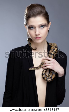 Young, beautiful, sensual woman with snake around her neck; a lot of copyspace available