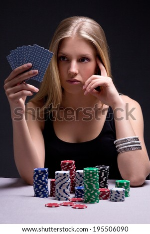 young beautiful serious woman playing poker in casino