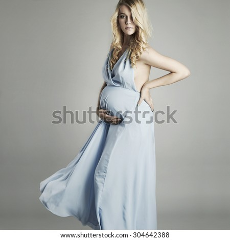 Young beautiful sexy and stylish pregnant woman in blue dress.Blonde - stock photo
