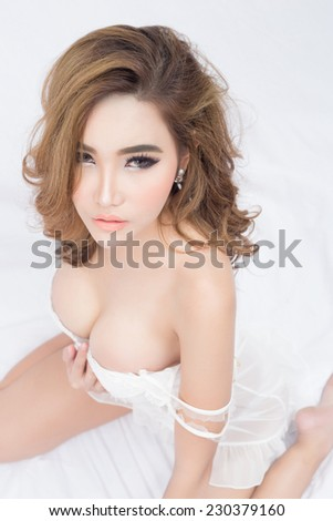 Young beautiful Sexy Asian model wearing elegant lingerie posing on bed - stock photo