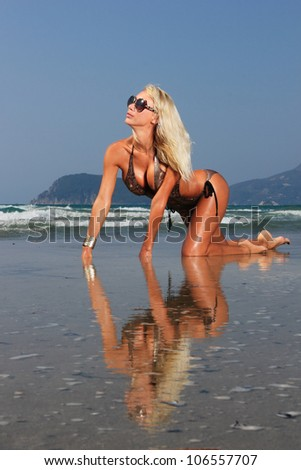Young beautiful sexy blond bikini model on a beach