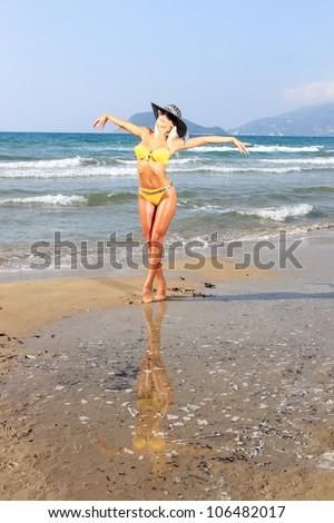 Young beautiful sexy blond woman with hat on a beach