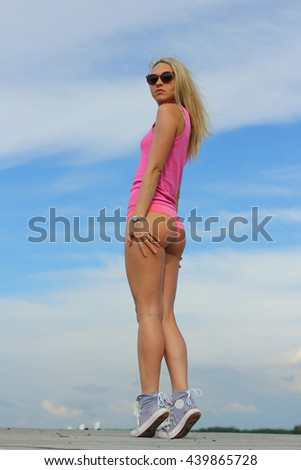 Young beautiful sexy booty dancer posing on blue sky background. Summer close up of hot blonde girl wearing mini trousers,swag black glasses, blue sneakers.  - stock photo