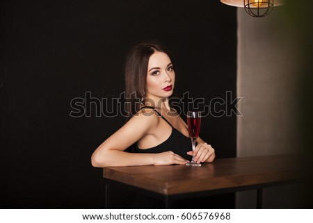 Young beautiful sexy brunette woman wearing black evening dress with decollete, makeup with red lips and hairstyling sitting at the table with a glass of wine. Fashion vogue style concept.