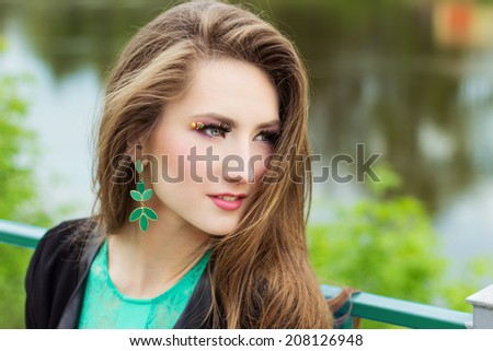 young beautiful sexy girl in a green dress with beautiful makeup with green shackles sitting on the river Bank in the city - stock photo