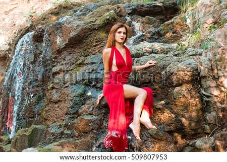 young beautiful sexy girl in a red dress on a waterfall