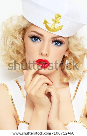 Young beautiful sexy girl with blond curly hair and stylish make-up dressed as sailor - stock photo