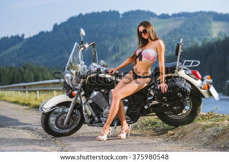Young beautiful sexy girl with long hair wearing swimming suit and high heels sitting on custom made cruiser motorcycle. Motorcycle is standing on the side of the road in the mountains. - stock photo