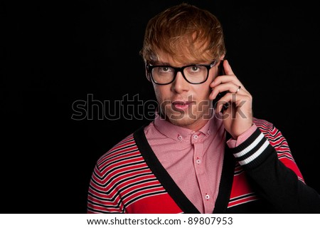 young beautiful sexy smart classy guy with glasses talking on a cell phone, on a black background