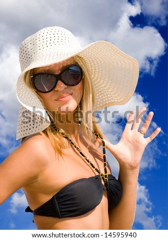 Young beautiful sexy tanned blond woman with hat and bikini laying on sea beach - stock photo