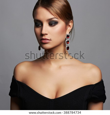 young beautiful sexy woman in black dress and jewelry.Beauty girl with make-up.elegant lady - stock photo