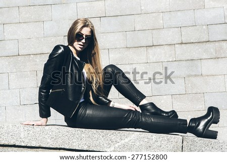 Young beautiful sexy woman in black skin clothes happy outdoors - stock photo
