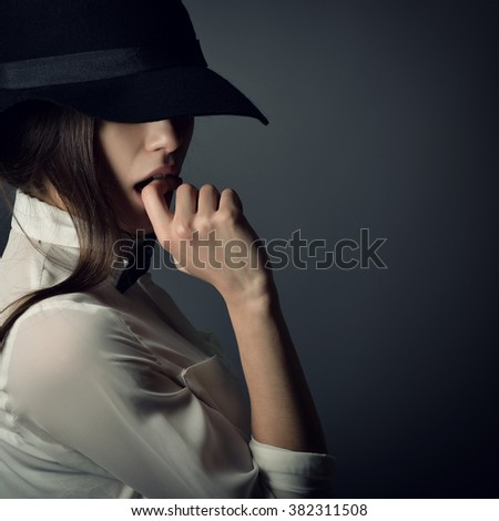 Young beautiful sexy woman in jacket, white shirt, bow-tie and hat over gray background. Fashion female portrait. Tomboy. Girl gets on men's clothes.