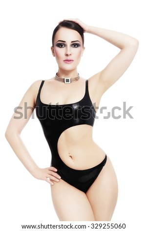 Young beautiful sexy woman in latex swimsuit over white background