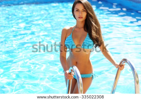 Young beautiful sexy woman standing in blue water of swimming pool. Pretty girl with log dark hair posing outdoor on a hot summer sunny day                                - stock photo