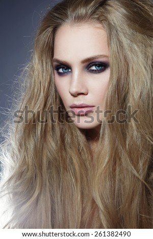 Young beautiful sexy woman with long blonde hair and smoky eyes - stock photo
