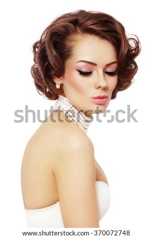 Young beautiful sexy woman with winged eyes make-up and curly hairstyle over white background