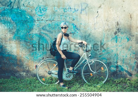 young beautiful short blue hair hipster woman with headphones music and bike in the city - stock photo