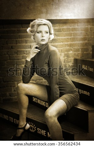 Young beautiful short hair blonde woman in turtle neck tight short dress sitting on stairs, black and white photo. Romantic mysterious lady with movie star retro look posing, bricks wall background. - stock photo