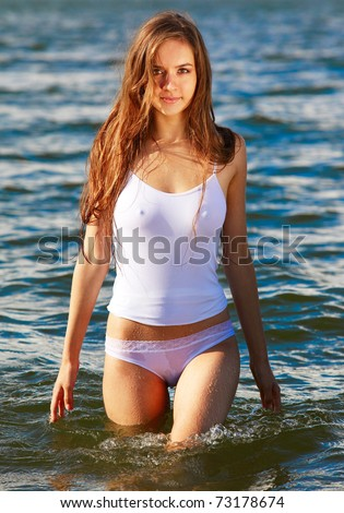 Young beautiful slavonic girl in white wet top and panties posing in the sea water - stock photo
