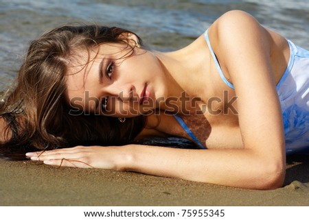 Young beautiful slavonic girl laying on the sand