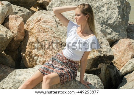 young beautiful slender girl is resting on the sea lying on the rocks
