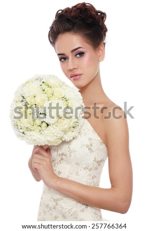 Young beautiful slim bride with stylish make-up and hairdo holding bouquet in her hand over white background - stock photo