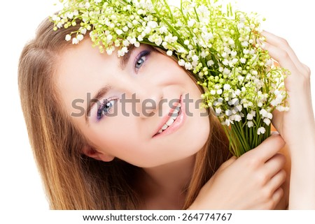 Young beautiful smiling blond woman holding lilies of the valley