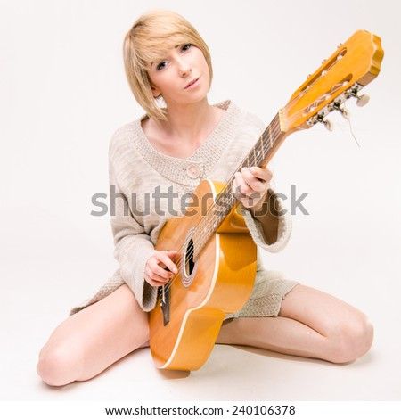 Young beautiful smiling blonde lady in gray sweater playing acoustic guitar - stock photo