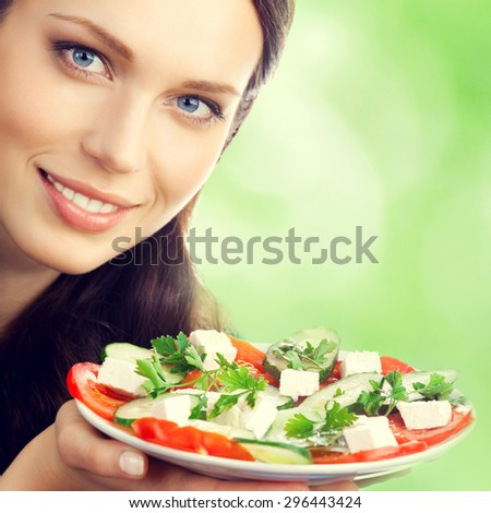 Young beautiful smiling brunette woman with plate of salad, outdoor - stock photo