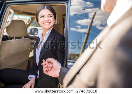 Young beautiful smiling businesswoman in suit coming out of her luxurious car. - stock photo