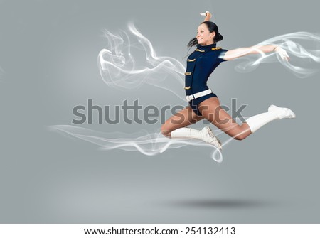 Young beautiful smiling cheerleader girl jumping high