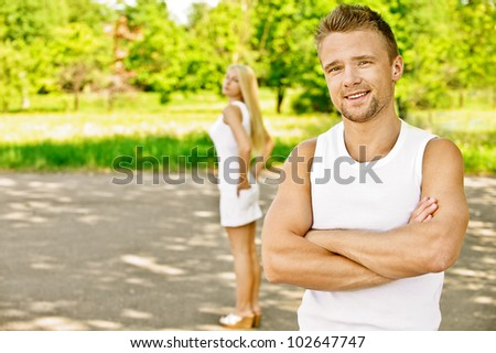 Young beautiful smiling couple dressed in white, against green of summer park.