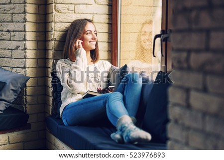 Young beautiful smiling girl in a white sweater and jeans sitting on the window sill and listening to music