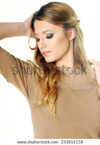 Young beautiful smiling long haired blond girl posing with her hand behind her head and looking down and away wearing a beige dress and perfect evening make up  isolated on White background - stock photo