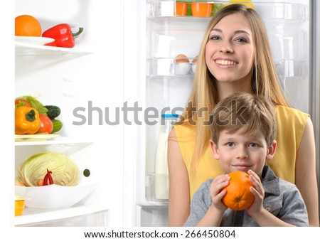 Young beautiful smiling mother and her little son with orange looking at camera near open fridge. Vegetables and fruits in the refrigerator - stock photo