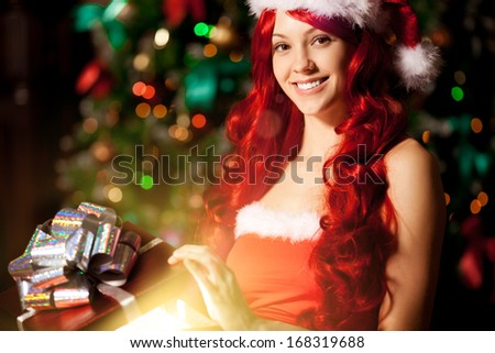 Young beautiful smiling santa woman near the Christmas tree with bunny. Fashionable luxury  girl celebrating New Year holding gift in hands