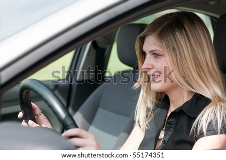 Young beautiful smiling woman driving car - portrait through side window - stock photo