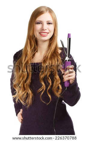 Young beautiful smiling woman in purple sweater with expressive hairstyle holding curling iron isolated on white background - stock photo