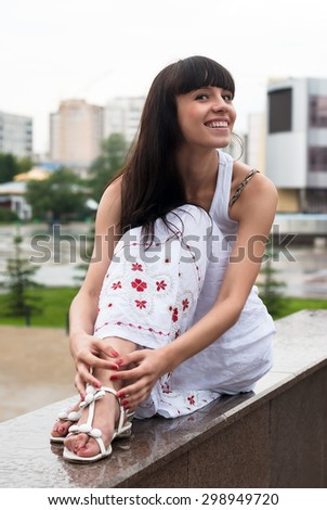 Young beautiful smiling woman sits over city background - stock photo