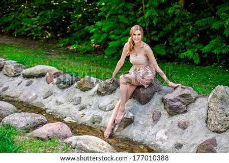 Young beautiful smiling woman sitting on rock by stream in park