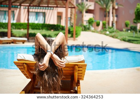 Young beautiful smiling woman swimmer relax on a lounger by the pool.