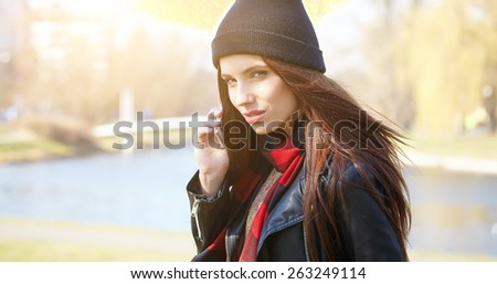 Young beautiful smiling woman talking on cell phone - stock photo
